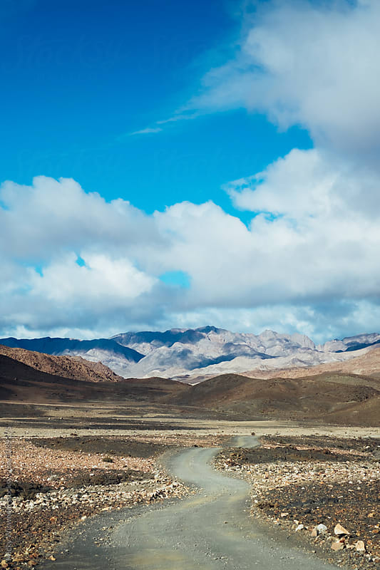 Remote winding desert road towards mountains by Micky Wiswedel for Stocksy United