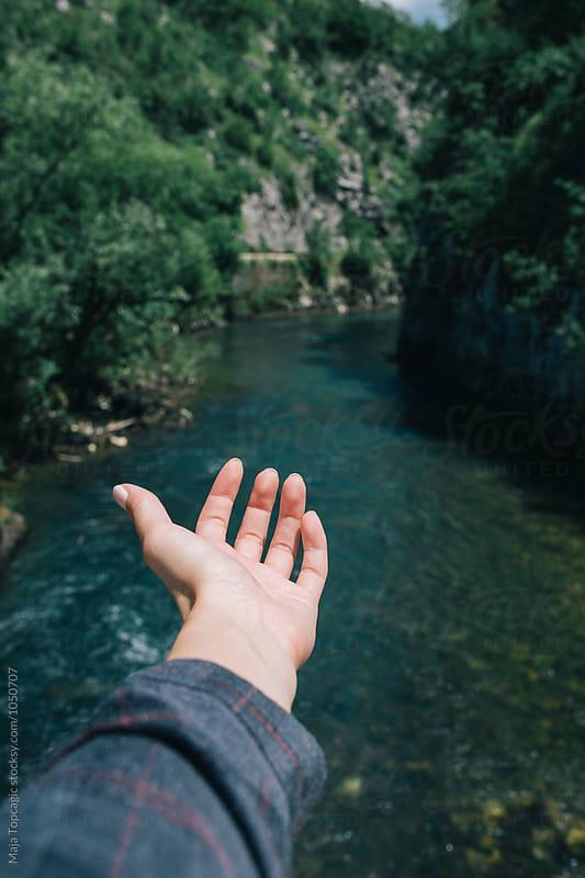 Female hand at a canyon by Maja Topcagic for Stocksy United