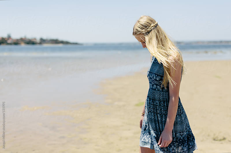 Teen girl wearing a blue summer dress walks by a river by Jacqui Miller for Stocksy United