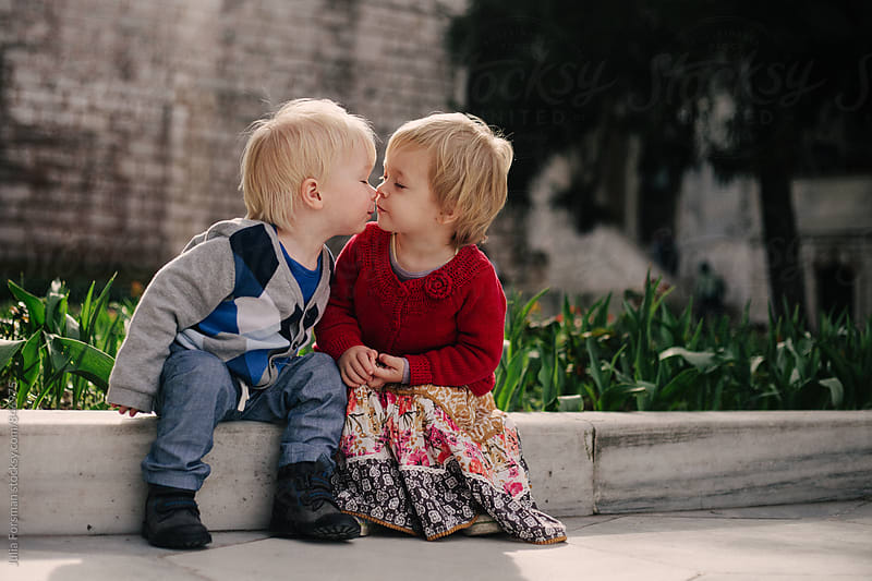 Two small children sitting on a low wall share a kiss. by Julia Forsman for Stocksy United