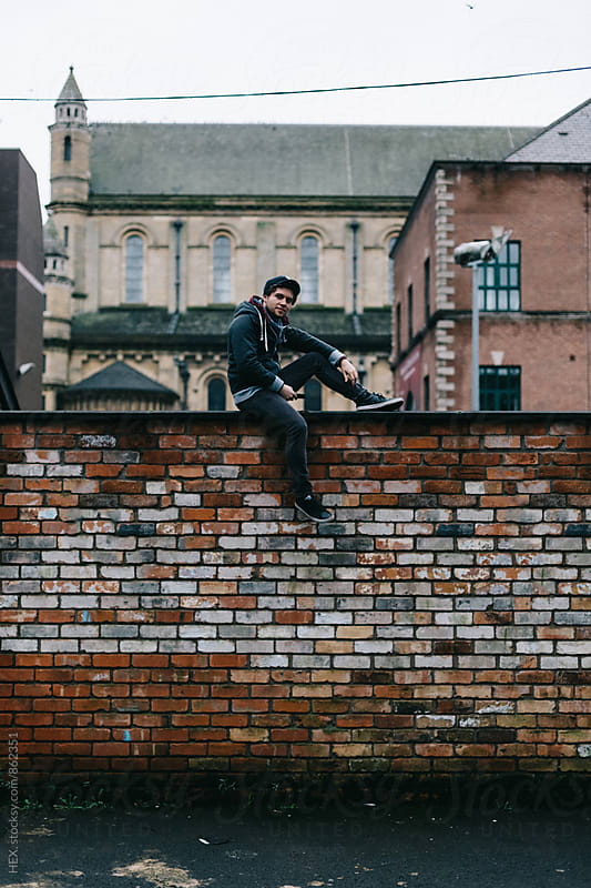 Young Man Standing on a High Wall in the City by Mattia Pelizzari for Stocksy United