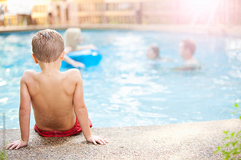 Swimming: Boy Sits By Pool For Time-Out or Rest by Sean Locke for Stocksy United