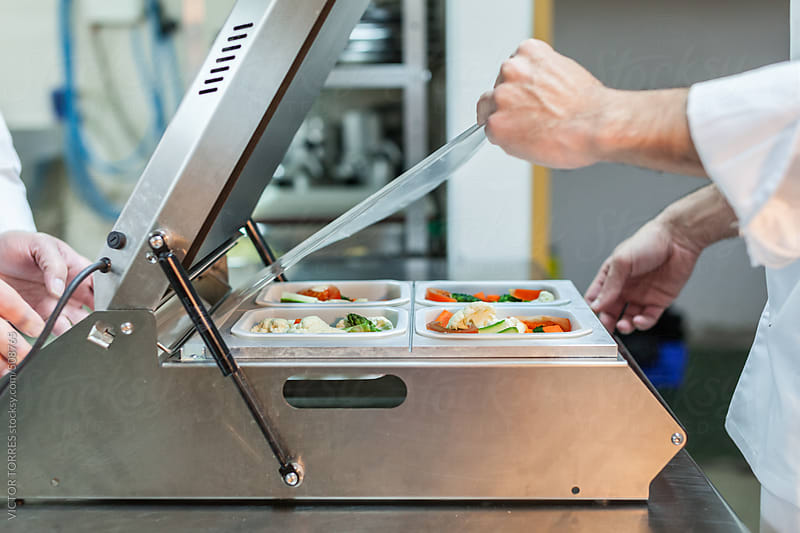 Chefs Shrink Wrappping Food with a Small Packaging Machine by VICTOR TORRES for Stocksy United