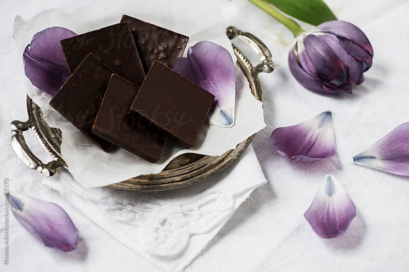 Tray of dark chocolate squares with lavender tulips by Rhonda Adkins for Stocksy United