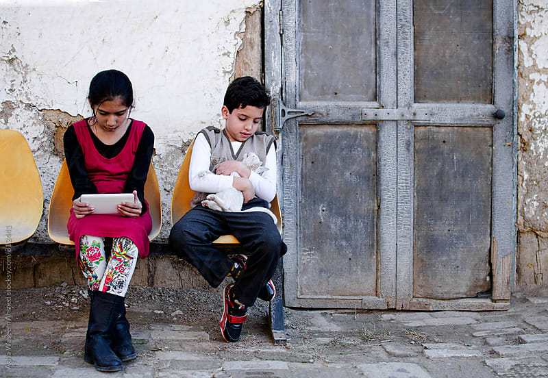 Two children , one holding a white kitten the other one using her tablet ! by Agha Waseem Ahmed for Stocksy United