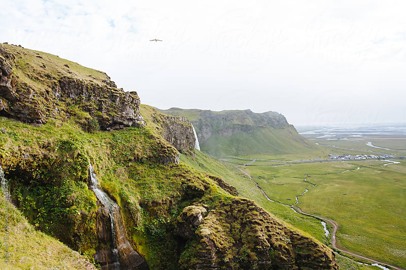 Pictoresque volcanic hill with multiple waterfalls, Iceland by Gabriel Tichy for Stocksy United