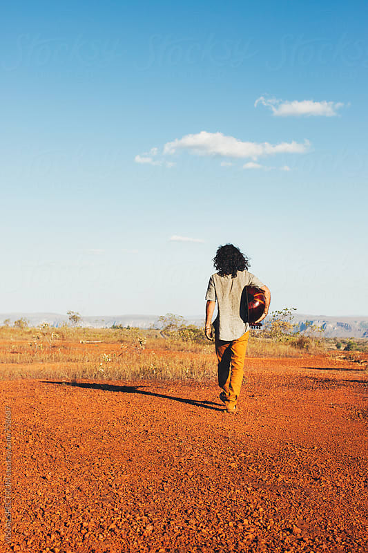 Long-Haired Man Holding Mandolin (Oud) and Walking Alone in Beautiful Countryside by VISUALSPECTRUM for Stocksy United
