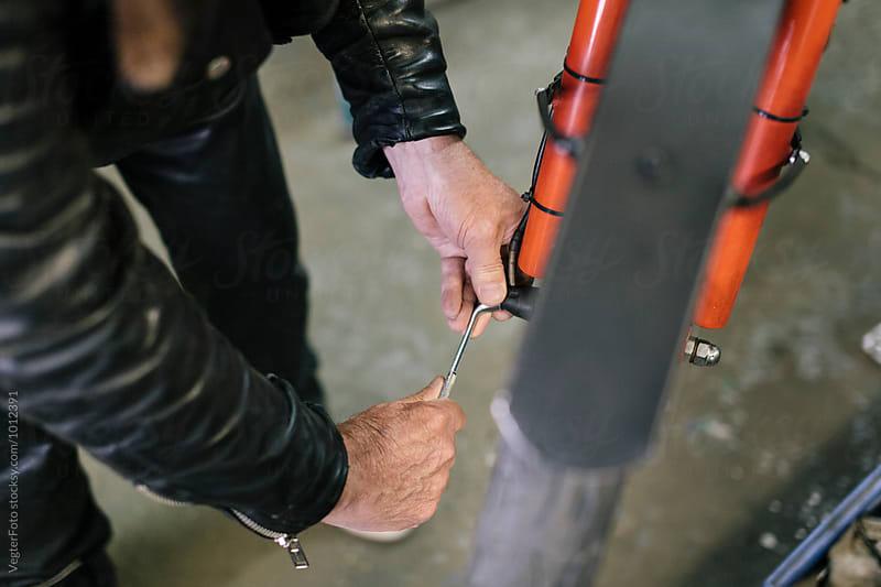 Senior Bicycle Mechanic tighting bolt by VegterFoto for Stocksy United
