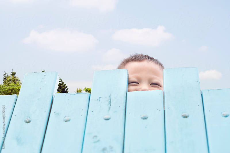 Child smile and hiding himself behide wooden fence by Lawren Lu for Stocksy United