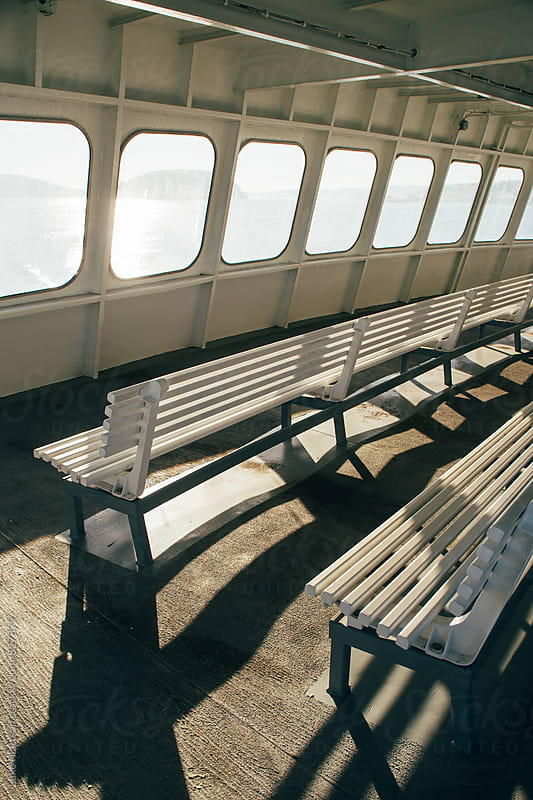 Windows And Benches Illuminated By Sunlight On Upper Deck of Passenger Ferry Boat by Luke Mattson for Stocksy United