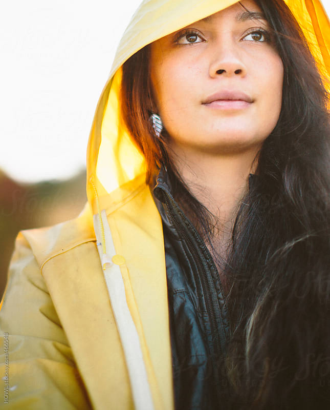 Young brunette girl wearing a yellow rain jacket on a fall day by HOWL for Stocksy United