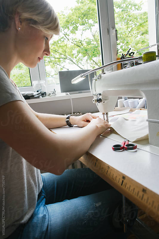 Profile of Caucasian Woman Working on Sewing Machine by VISUALSPECTRUM for Stocksy United