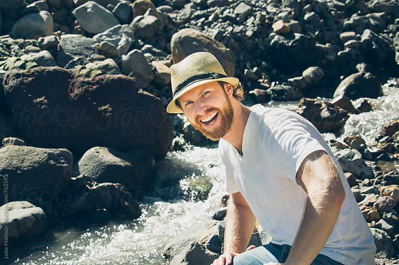 Bearded Blond Man Wearing Fedora And Smiling While Sitting On River Rocks by Luke Mattson for Stocksy United