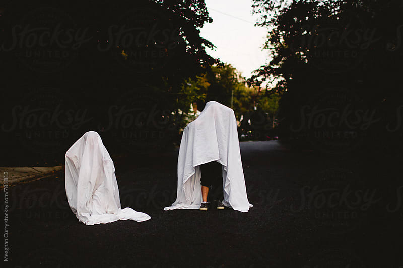 two children dressed in ghost costumes for halloween by Meaghan Curry for Stocksy United