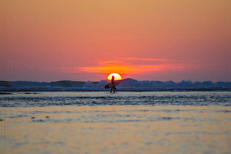 Surfer in front of setting sun by Felix Hug for Stocksy United