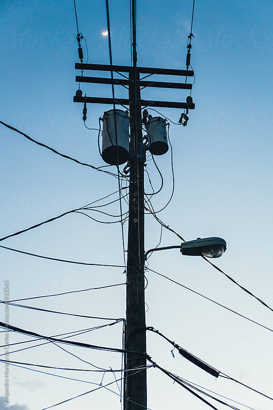 Electric high voltage pillar with many cables at dusk by Alejandro Moreno de Carlos for Stocksy United