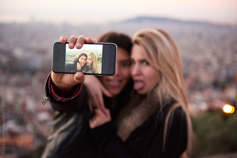 Two young women sticking out tongues while taking selfie by Guille Faingold for Stocksy United