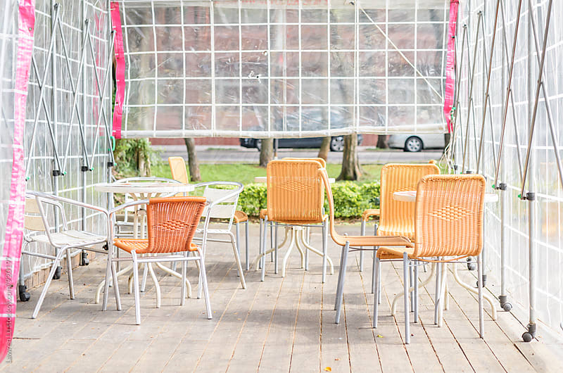 Table and chair of outdoor cafe under clear canopy by Lawren Lu for Stocksy United