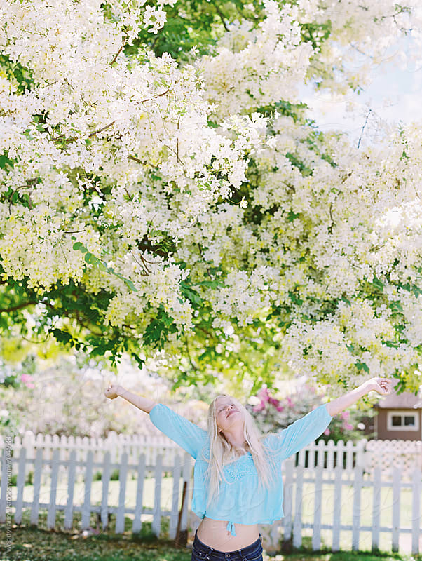 blonde girl yelling for joy in front of showering floral tree by wendy laurel for Stocksy United