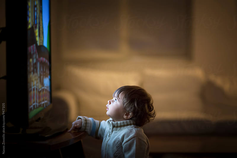 1 year old boy watching  television in the dark by Nasos Zovoilis for Stocksy United