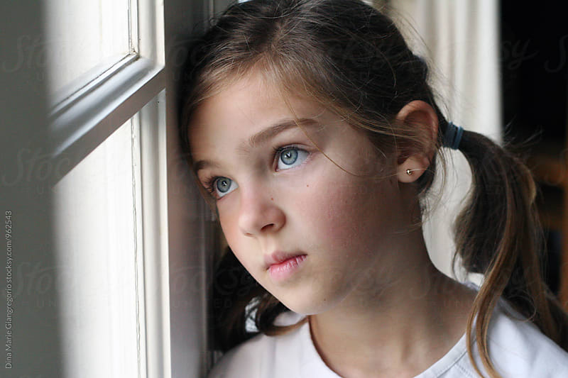 Girl With Pigtails Leaning Head Against Window Looking Out by Dina Giangregorio for Stocksy United