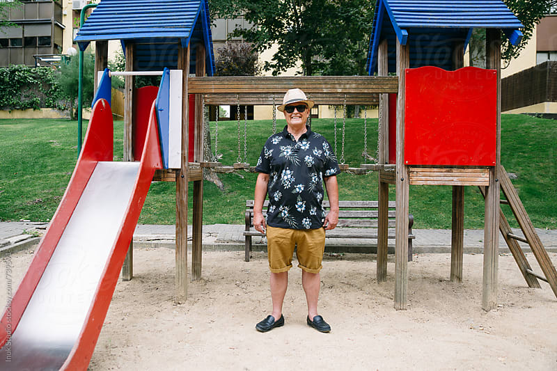 Stylish senior man wearing sunglasses and a straw hat in a children park by Inuk Studio for Stocksy United