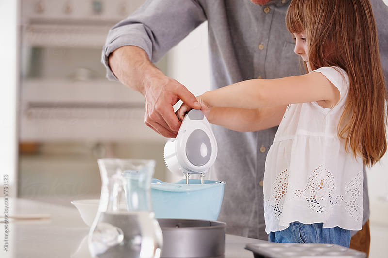 Father and daughter baking a cake by Aila Images for Stocksy United