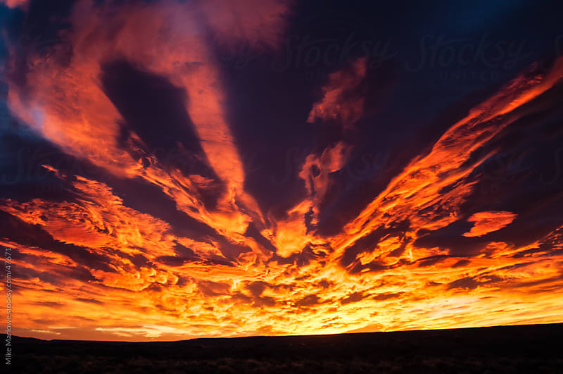 A dramatic and colourful sunrise with bright red and orange light by Mike Marlowe for Stocksy United