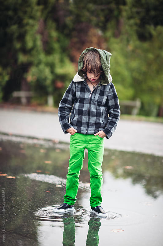 Boy standing in a large puddle of water by Angela Lumsden for Stocksy United