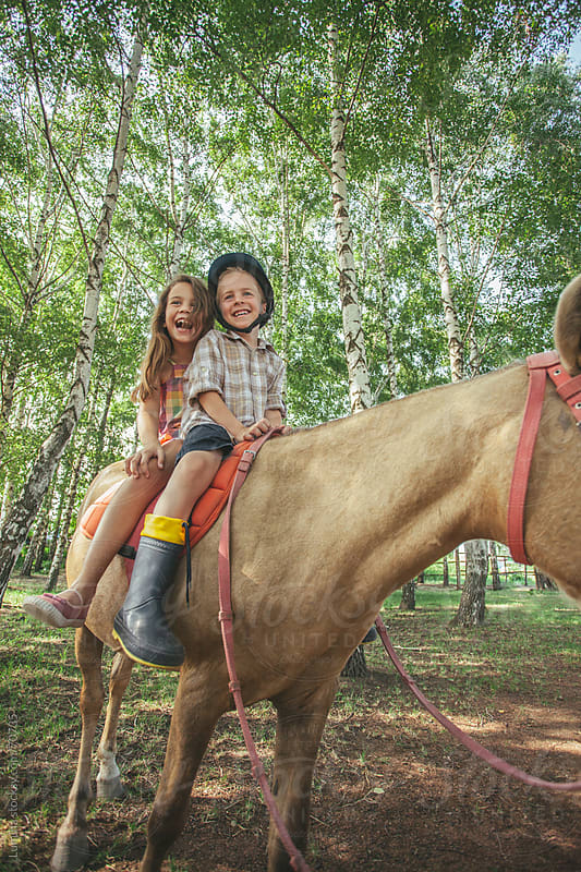Boy and Girl Riding a Horse by Lumina for Stocksy United
