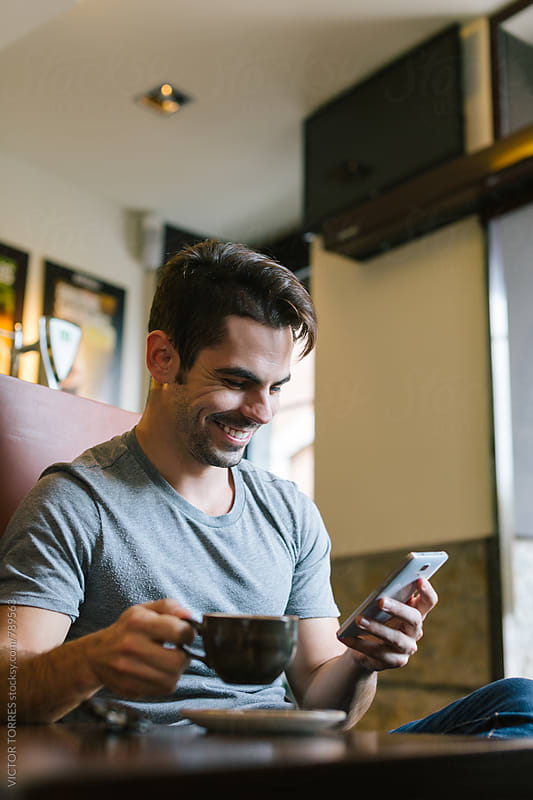 Young Man Using a Phone in a Coffee Shop by VICTOR TORRES for Stocksy United