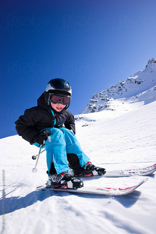 Young boy snow skiing downhill by J.R. PHOTOGRAPHY for Stocksy United