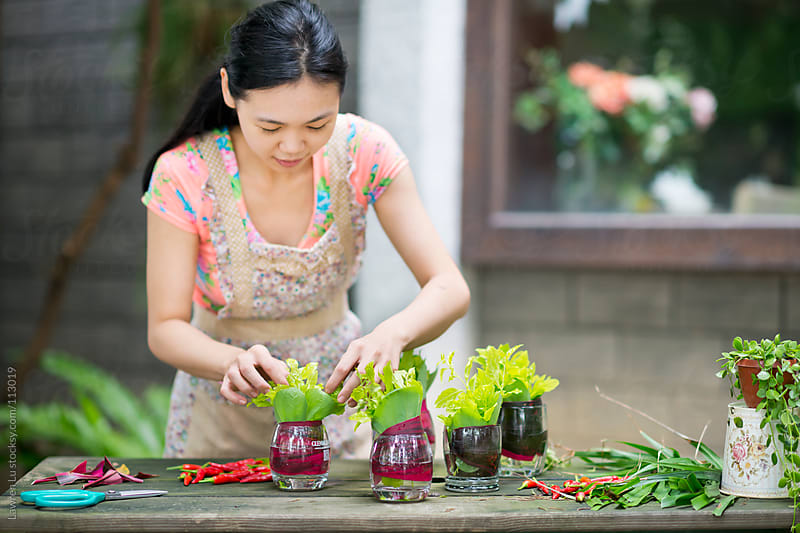 Woman cutting plants for flower arrangement decoration by Lawren Lu for Stocksy United