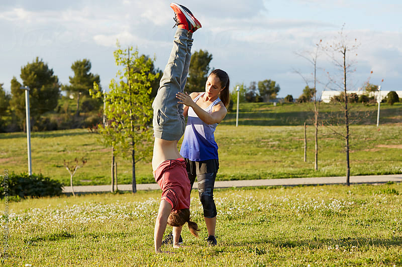 Instructor Assisting man With Handstand In Park by ALTO IMAGES for Stocksy United