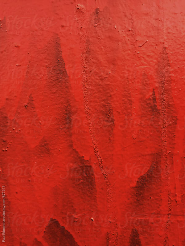 Bright red paint covering graffiti on wall, close up by Paul Edmondson for Stocksy United