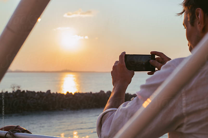 Man taking a photo of a beautiful sunset by Jovo Jovanovic for Stocksy United
