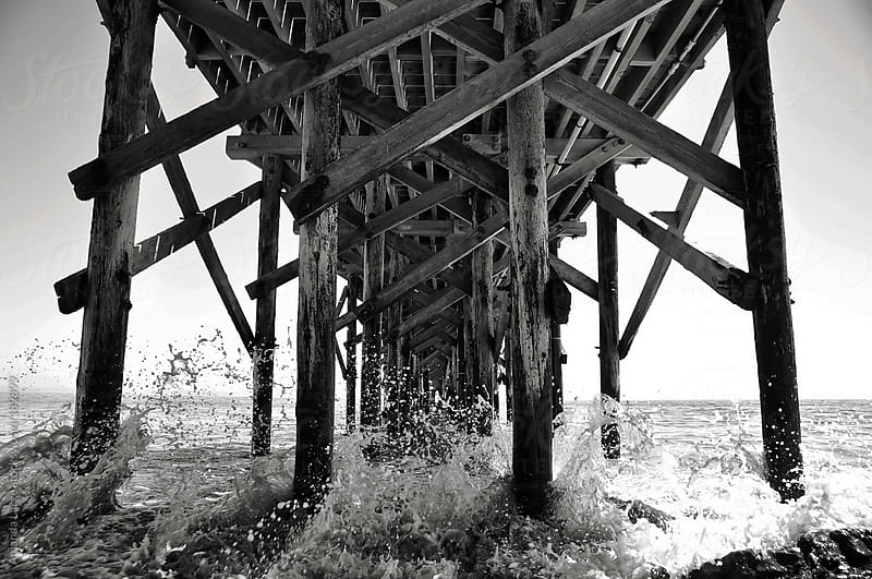 Underside of a wooden pier at the beach by Amanda Large for Stocksy United