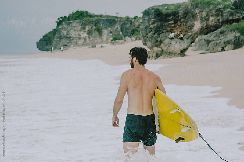 A surfer walking in to the water by Joseph West Photography for Stocksy United