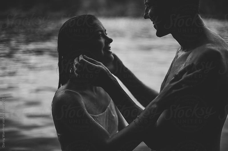 Intimate engaged couple soaking wet in a lake by Daring Wanderer for Stocksy United