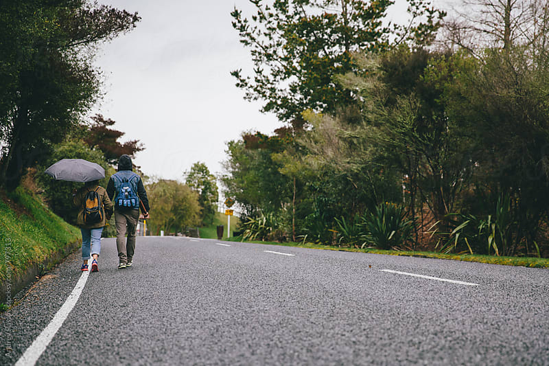 Couple of backpackers walking along the road by Andrey Pavlov for Stocksy United