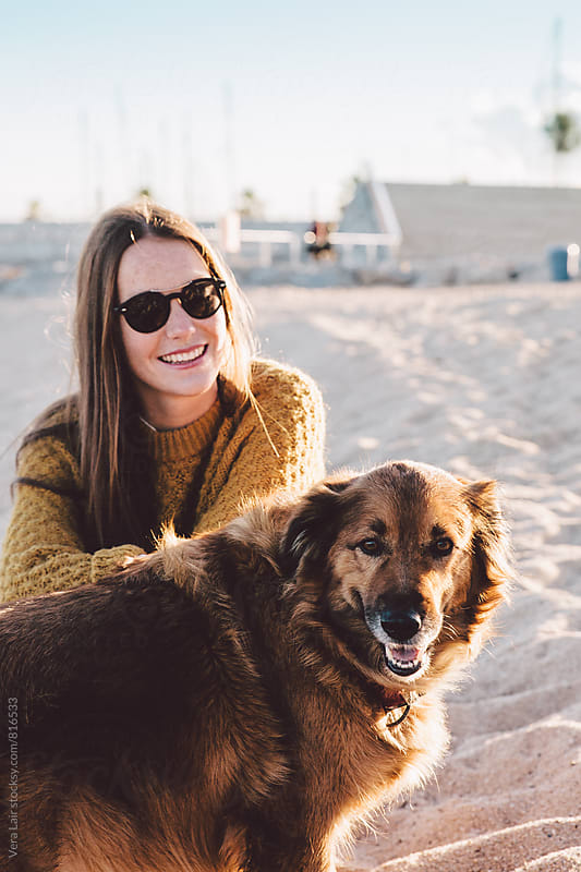 Pretty woman with a red dog at the beach by Vera Lair for Stocksy United