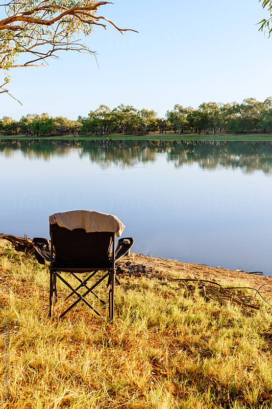 empty camp chair by a river in outback Australia by Gillian Vann for Stocksy United