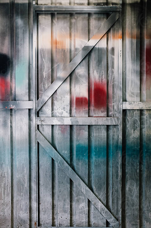 Colourful spray painted door inside paint shed by Jacqui Miller for Stocksy United