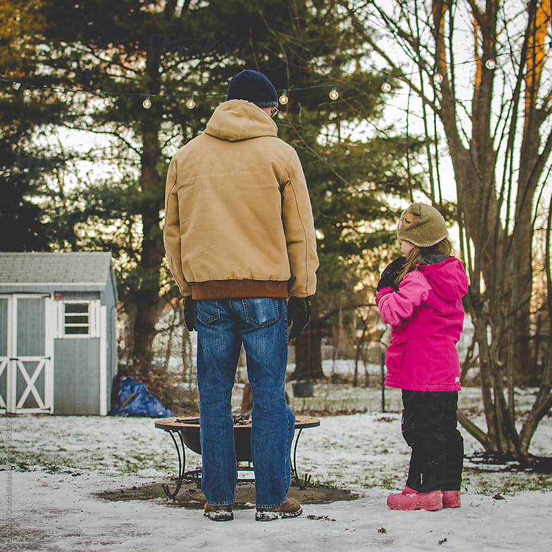 Father and daughter standing by fire pit in winter by Lindsay Crandall for Stocksy United