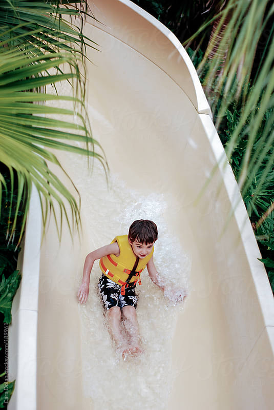Child wearing life jacket rides down a water slide by Cara Dolan for Stocksy United
