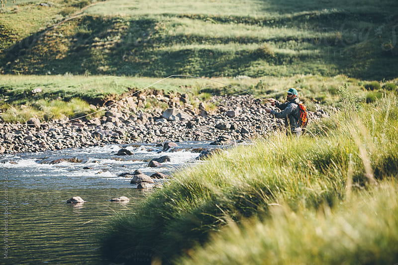 Fly fisherman casting into a river at dawn by Micky Wiswedel for Stocksy United