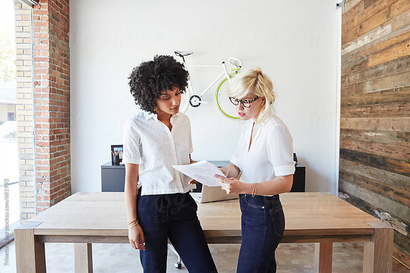 Portrait of millennial businesswomen in office looking at papers by Trinette Reed for Stocksy United