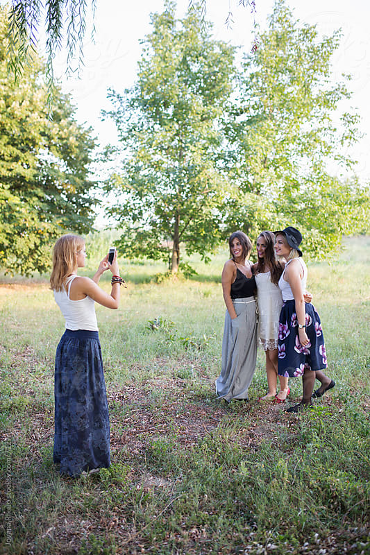 Four female friends, one taking photo of others by Jovana Rikalo for Stocksy United
