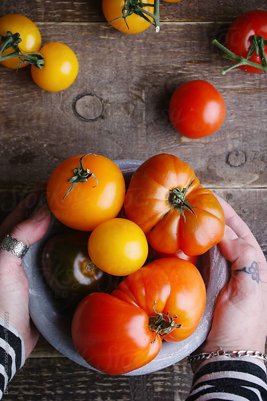 Closeup of a woman's hand on a bowl of mixed Heirloom or Heritage tomatoes. by Darren Muir for Stocksy United