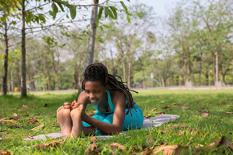 Beautiful young woman practicing yoga outdoors by Jovo Jovanovic for Stocksy United